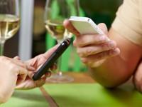 Paar sitzt gemeinsam schweigend mit Smartphones im Restaurant